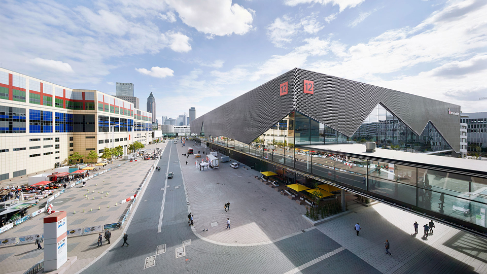 An exterior shot of the exhibition center. Hall 12 can be seen on the right, the glass staircase leading to it, and another exhibition building on the left. A large road runs in between.