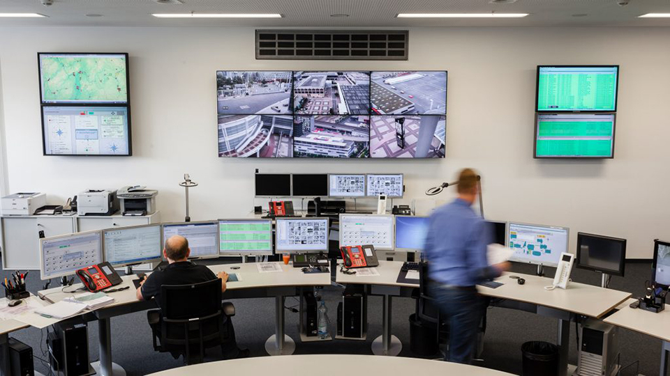 View of the control center of the Operation Security Center at Messe Frankfurt. There are several surveillance screens on the wall and on the desks. One employee looks at one of the screens, the other employee is walking to his seat.