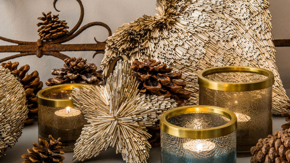 Storm lights are surrounded by pine cones and decorative elements made of reed.
